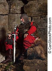 Old medieval King in armor with sword is sitting on furs near the camp fire