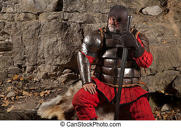 Old medieval King in armor with sword is sitting on furs