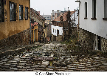 Old medieval narrow stone paved street in Buda district of of Budapest on a foggy day in winter. Shot at Gul Baba utca