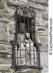 Old medieval stone statue in wall of Virgin mary with child