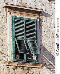 old mediterranean window with green shutters