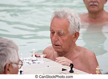 Old men playing chess in pool