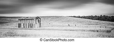 Old Metal Barn in a Field with Motion in Clouds B&W