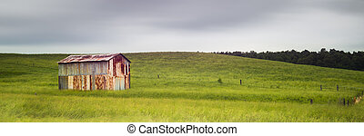 Old Metal Barn in a Field with Motion in Clouds
