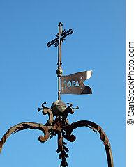 old metal cross against the sky