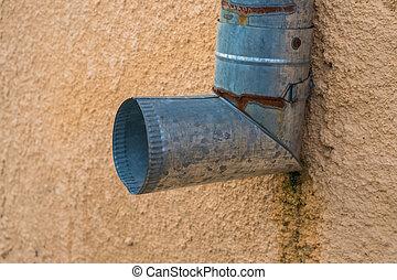old metal drainpipe on an orange wall.
