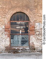 Old metal glass window, on weathered wall.