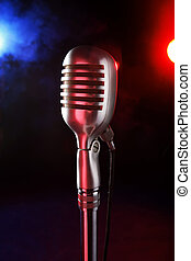 old microphone on a dark background and smoky