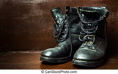 Old military boots against wooden background