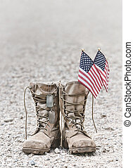 Old military combat boots with dog tags and two small American flags