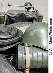 Old military helmet. Detail with old military helmet placed over car tire.