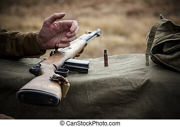 Old military rifle. Next to the rifle shell casing and...
