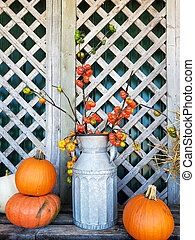 old milk can with autumn pumpkins