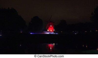 old mill illuminated laser red light park evening light...