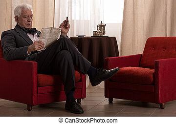 Old millionaire smoking cigar