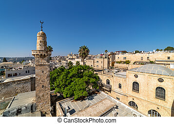 Old minaret among typical houses under blue sky in Old City of Jerusalem.