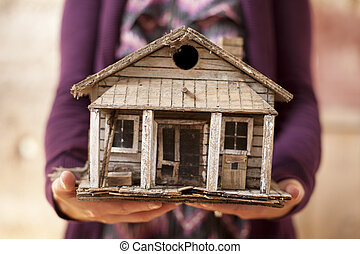 Woman holding old minature house that is falling apart.