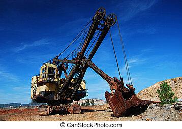 Old mining big machines backhoe - bulldozer working in old development.