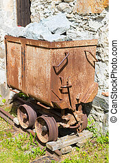 Old mining truck in front of the Health resort Heilstollen, a former mining tunnel. Near Bad Gastein, Austria, Europe. Hammer and pick as symbols of mining.