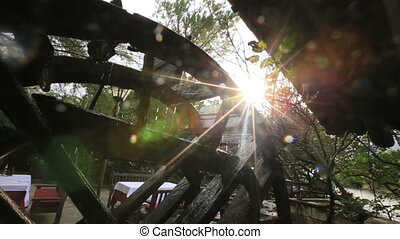 Old misterious mill in the dark woods with sunbeams close up