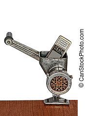 Old mobile phone in meat grinder on white background.