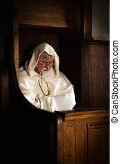 Old monk in dark church