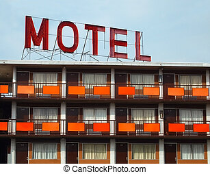 """Detail of a an old """"MOTEL"""" sign atop an old motel with many rooms."""