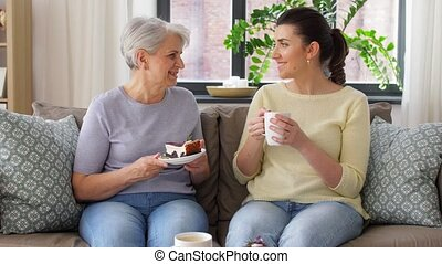 old mother and adult daughter eating cake at home - family, ...