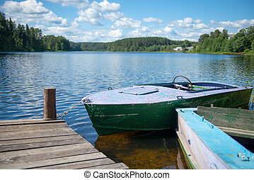 Old motor boat tied to a wooden pier on the lake