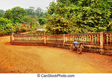 Old motorcycle against fence, African dirt road landscape