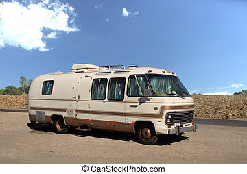 An old, dated motorhome in a country scene