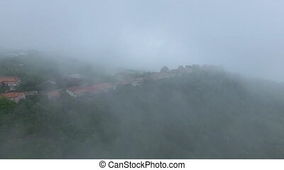 Old mountain town in a fog aerial view
