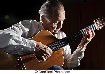 Old musician. - An elderly man in white shirt playing an...