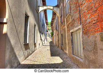 Old narrow street among ancient houses in Avigliana, Italy.