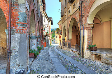Old narrow street among ancient houses in Avigliana, Italy.