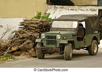 old off-road car beside the pile of firewoods