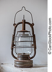 Old oil lamp against white wall
