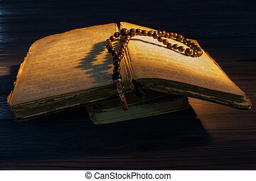 Old open bible with rosary beads.