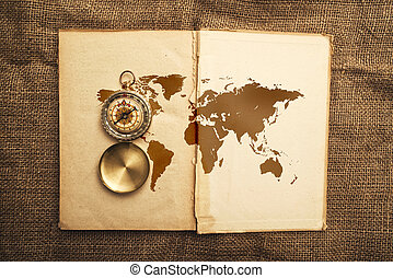 Vintage open book with old navigation compassand world map.