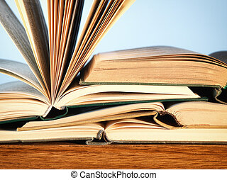 Old open novel books on a wooden table - Close-up of a pile...