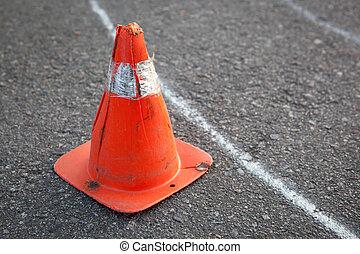 Old orange striped cone on road. - Old orange striped cone...