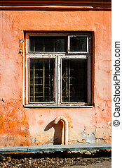 Old orange wall with a window