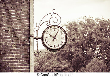 old Outdoor analog clock on a wall, vintage color filter