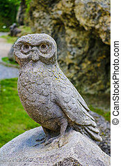 Old owl sculpture on stone in a park or garden.