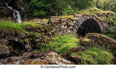 A packhorse bridge crossing a tributary below a waterfall on the south bank of the River Lyon. This is locally known as the Roman Bridge, though actually seems to date back to the 1600s or 1700s.