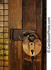 Old Padlock - Old padlock on a wooden door with grid