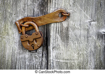 Old padlock on a wooden door - Old rusty padlock on a wooden...