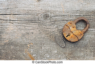 Old padlock over wooden background. With copy space
