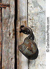 Old padlock - Rusted open padlock on the old wooden door