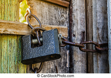 old padlock with chain on wooden gate